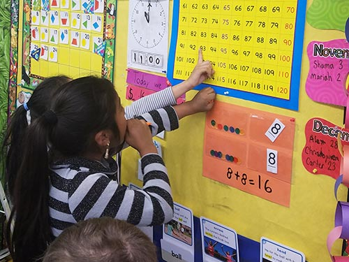 Young students study a chart of numbers