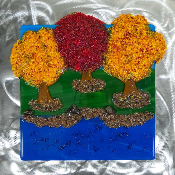 Glass sculpture of three trees on a lakeshore