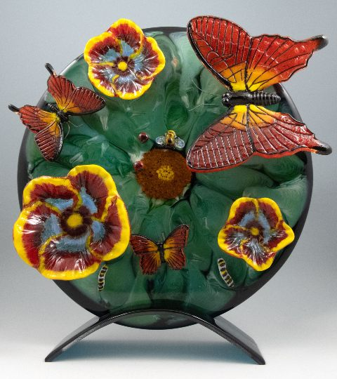 Glass art: 3D butterflies, caterpillars, and flowers on a green plate