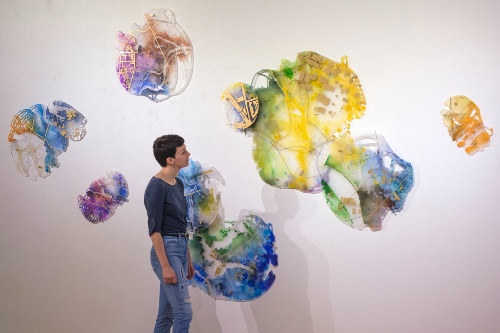 Young female student looking at a large wall installation of colorful abstract pieces