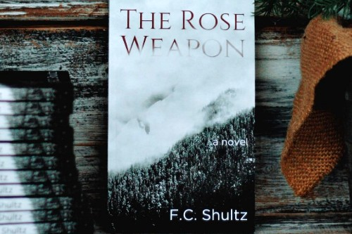 """Book cover of """"The Rose Weapon"""" with dragon swooping over mist-covered mountains"""