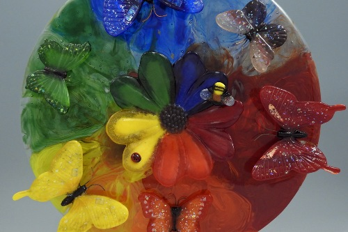 Three-dimensional butterflies and flowers on a rainbow-colored glass plate