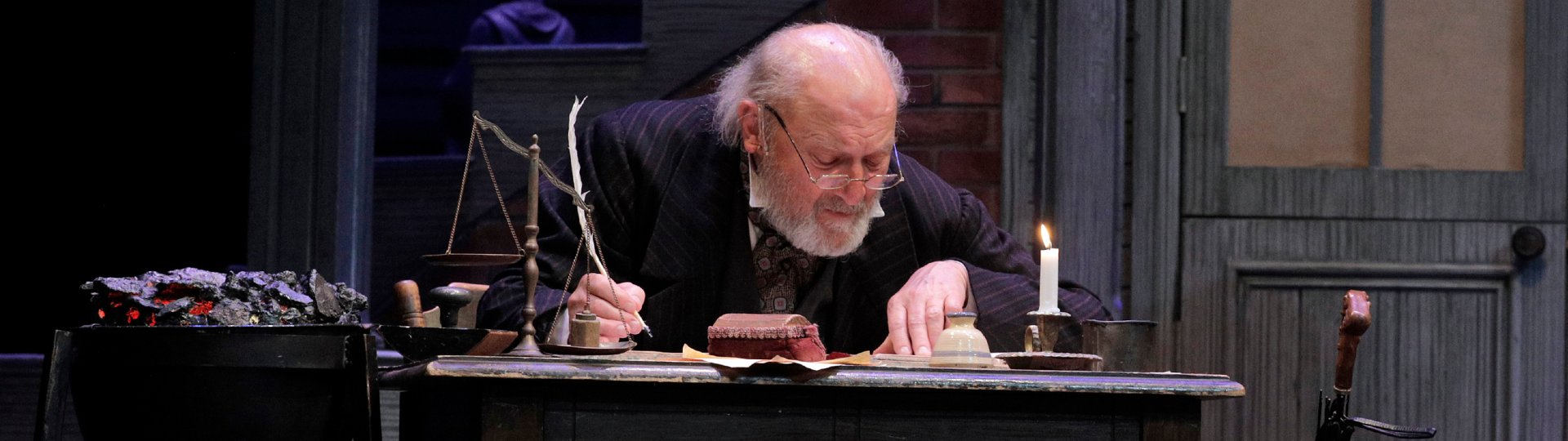 Old man in Victorian garb writing with a quill pen at a shabby desk