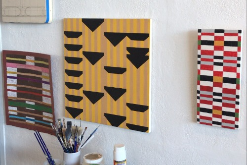 three abstract paintings on a white wall