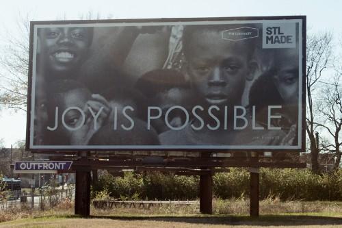 "Billboard showing Black children and words ""JOY IS POSSIBLE"""