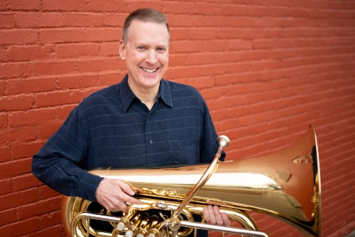 Man in blue flannel shirt smiling while holding tuba