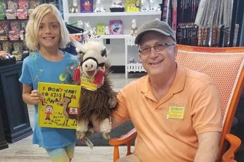 """Older man with llama puppet and young girl holding """"I Don't Want to Kiss a Lllama"""" book"""