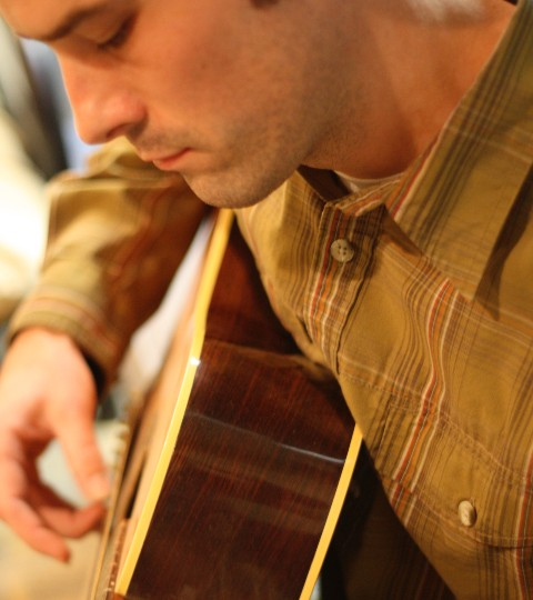 Young man with serious expression playing a guitar