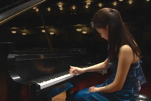 Young woman in evening gown with hand on piano keyboard