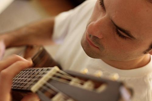 Closeup photo of man playing guitar