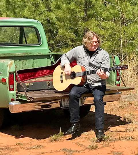 Photo of man playing sitting on tailgate of old pickup truck and playing guitar