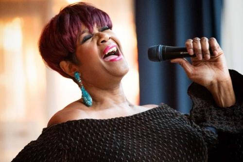 Woman singing, head thrown back, eyes closed