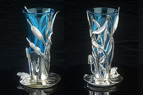 Two vases with silver frog sitting on base, blue glass surrounded by silver cattails
