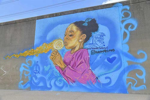 Mural covering full height of wall, young girl blowing dandelion puff